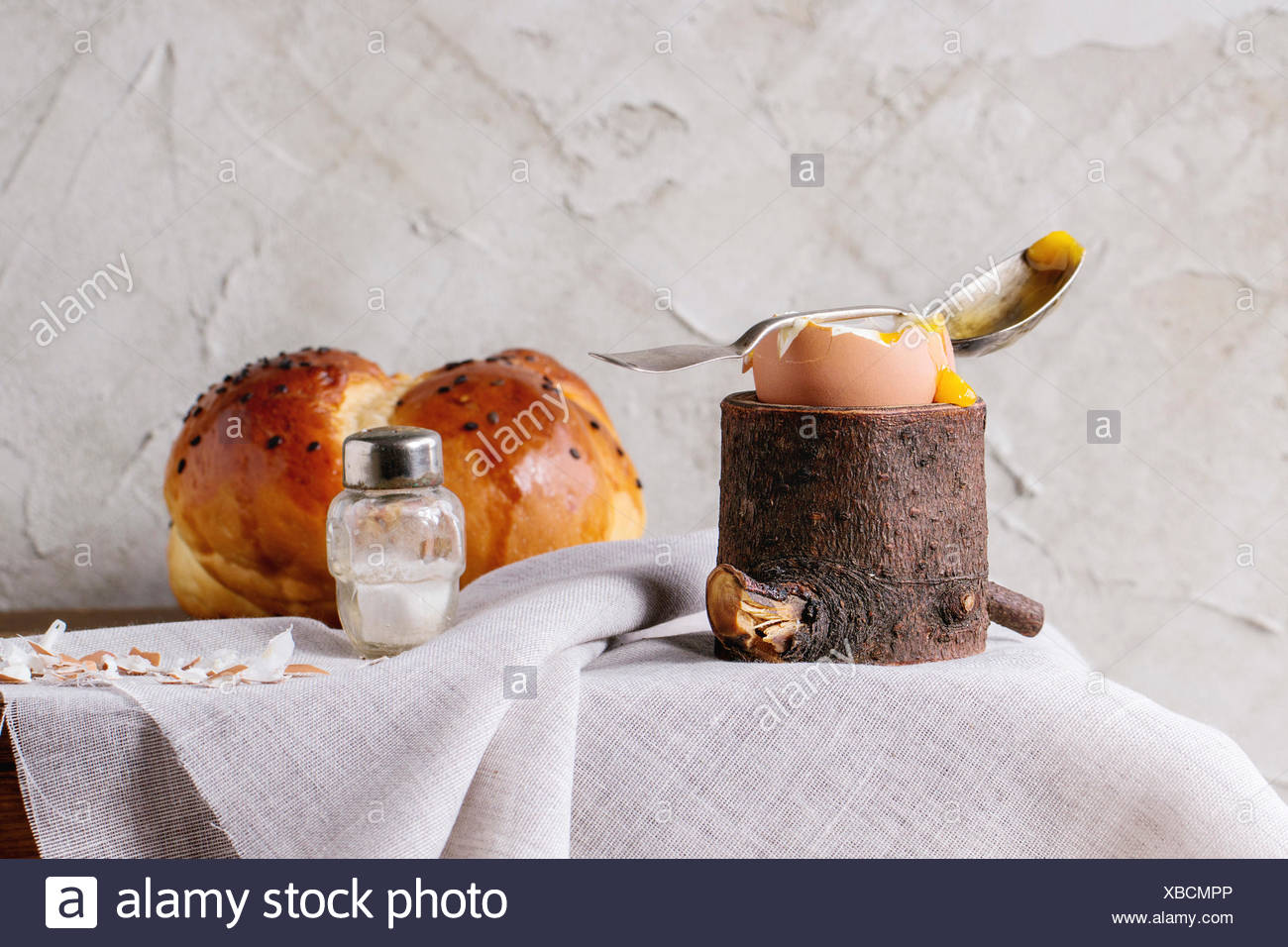 Breakfast with started eating soft-boiled egg with pouring yolk in wooden eggcup and home made bread served with salt and silver - Stock Image