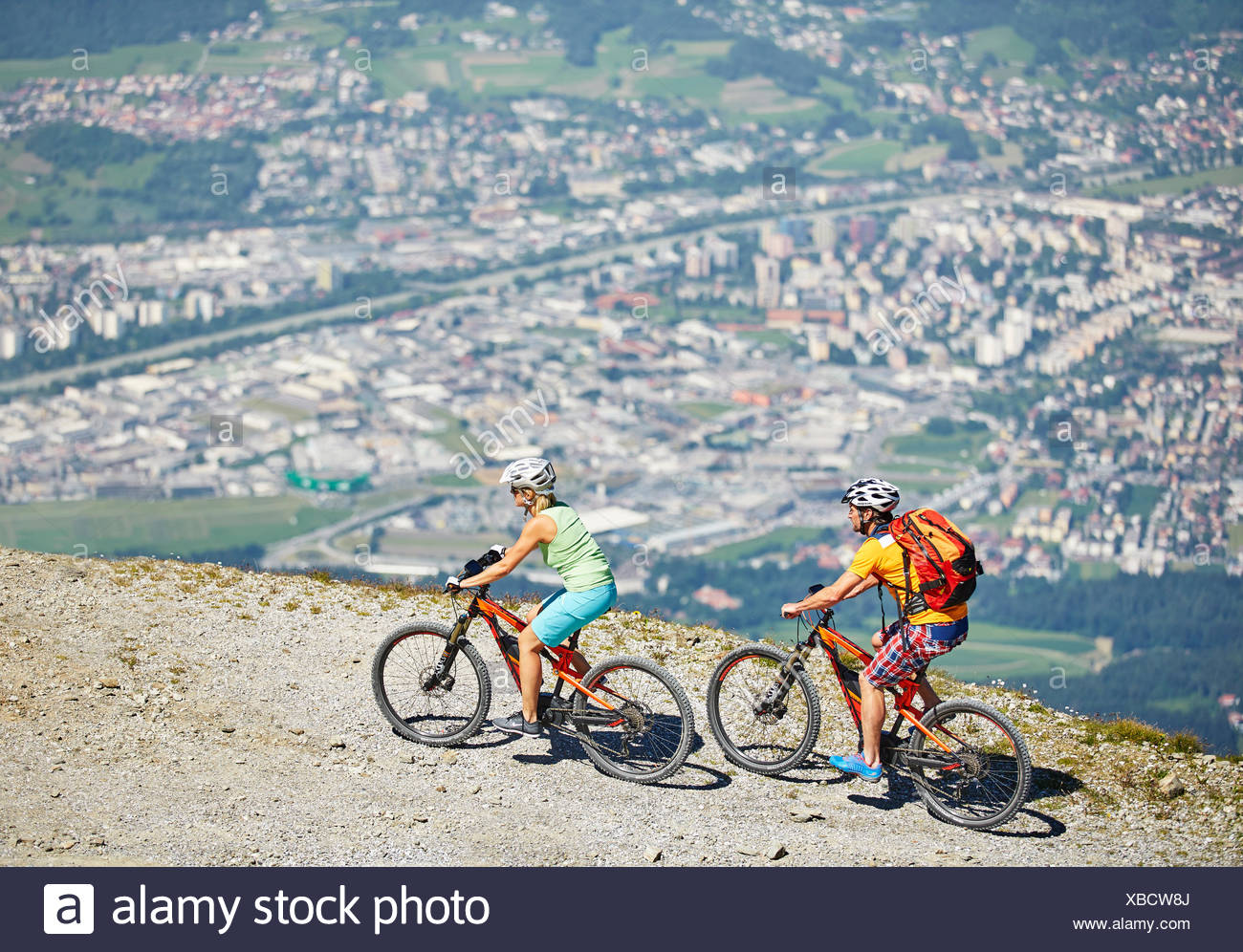 Man 40-45 years and woman 35-40 years with helmets cycle with their mountain bikes, Zirbenweg, Patscherkofel, Innsbruck, Tyrol - Stock Image