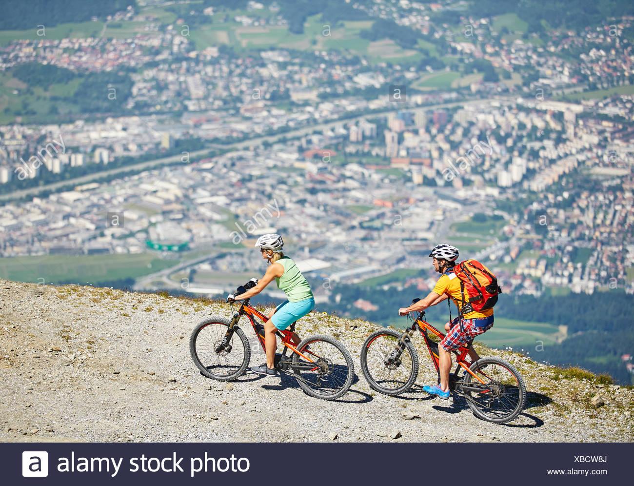 Man 40-45 years and woman 35-40 years with helmets cycle with their mountain bikes, Zirbenweg, Patscherkofel, Innsbruck, Tyrol Stock Photo