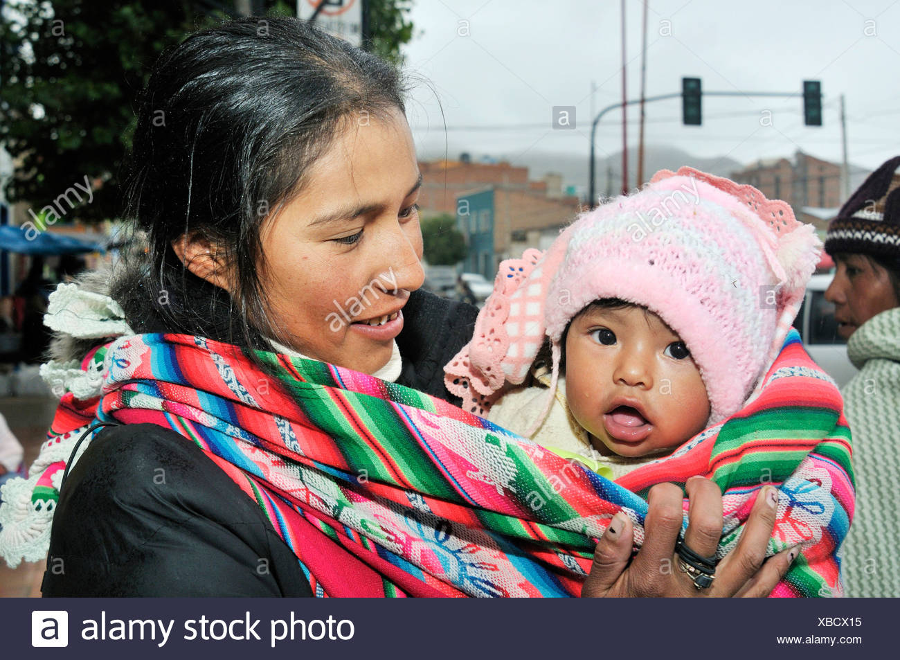 Young mother with baby in a baby-sling, Bolivian Altiplano highlands, Departamento Oruro, Bolivia, South America - Stock Image