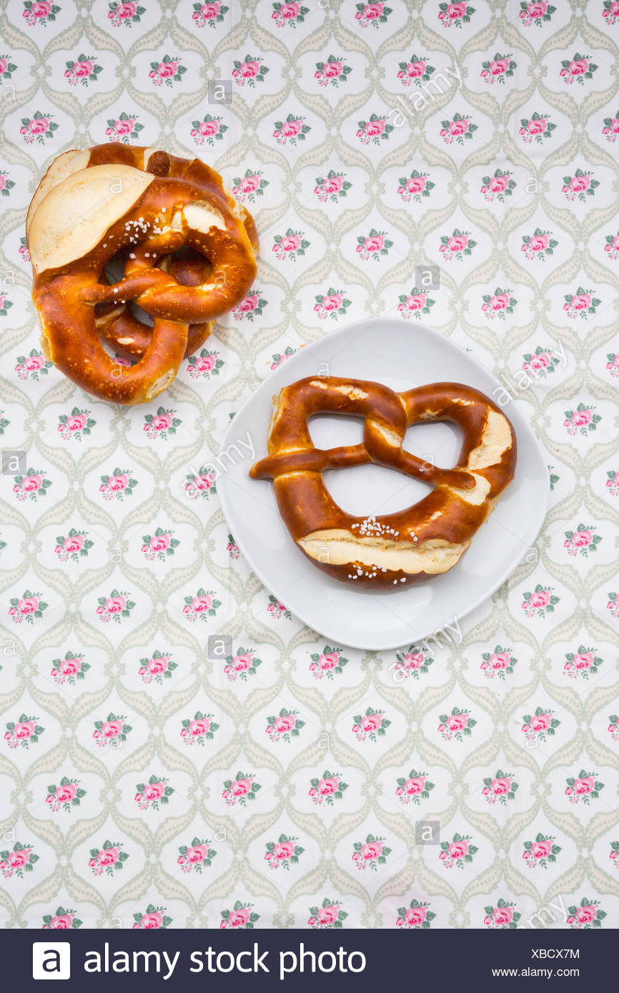 Dish and salted pretzels on table cloth with floral pattern - Stock Image