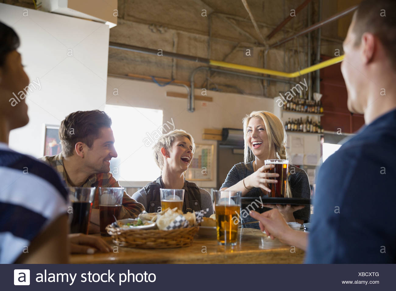 Waitress serving friends beer at brewery - Stock Image