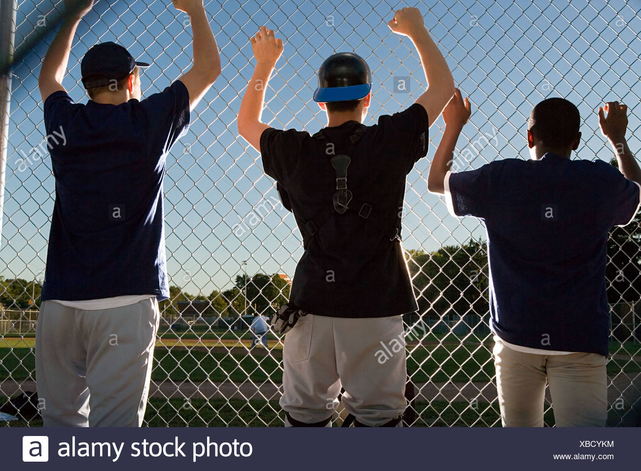 Three teenagers watching from the sidelines - Stock Image