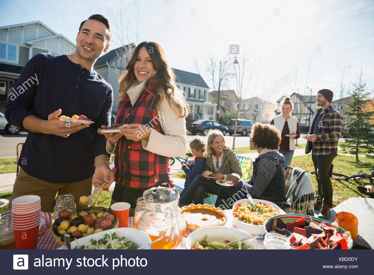 Neighbors enjoying potluck in sunny front yard - Stock Image