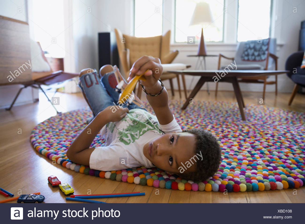 Boy playing with toy plane on rug - Stock Image