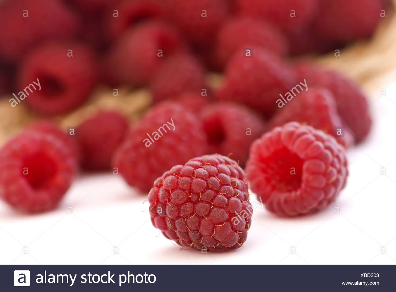 Fresh raspberry in and outside of a basket - Stock Image