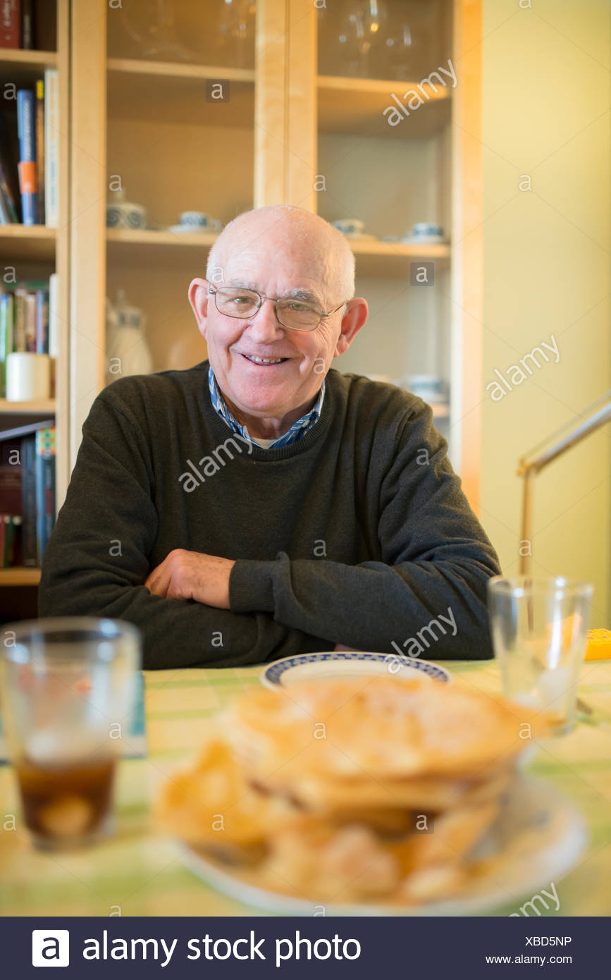 Portrait of smiling senior man sitting at laid table at home - Stock Image