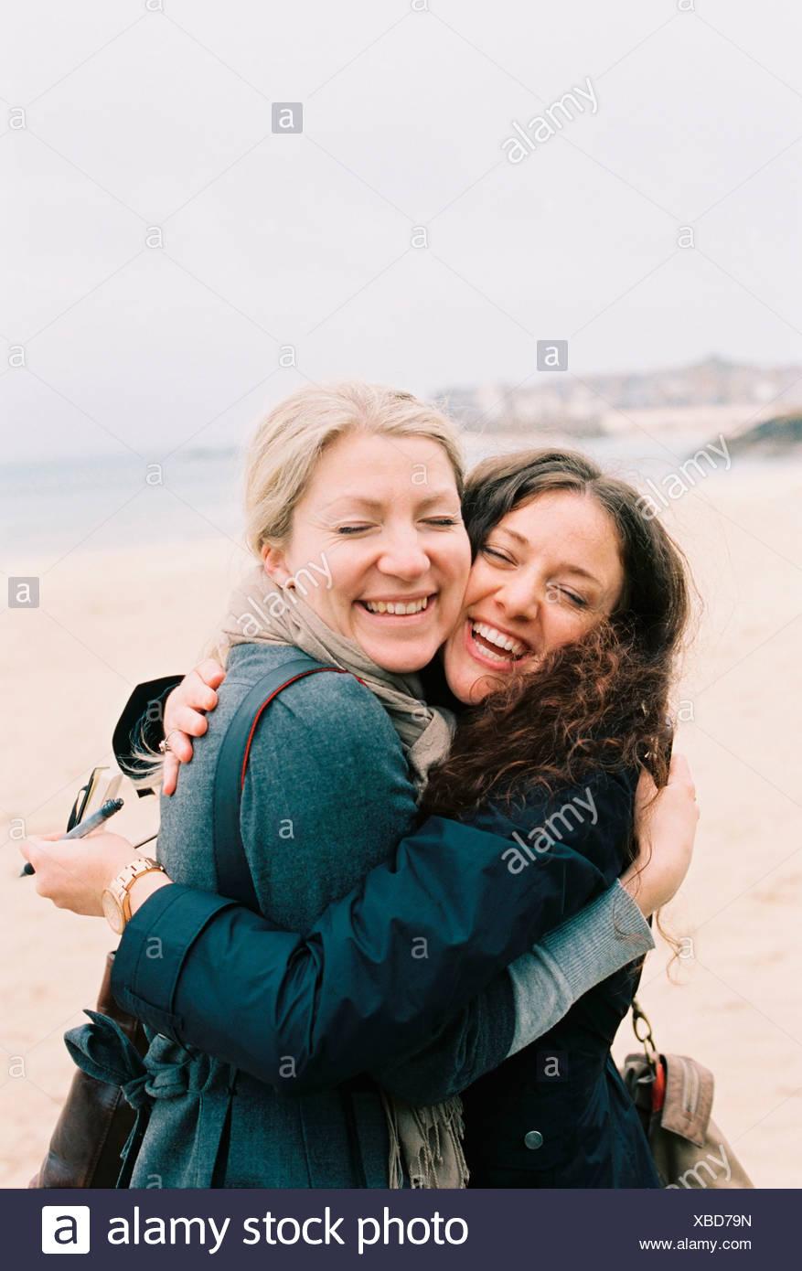 Two women cheek to cheek hugging on a beach. - Stock Image