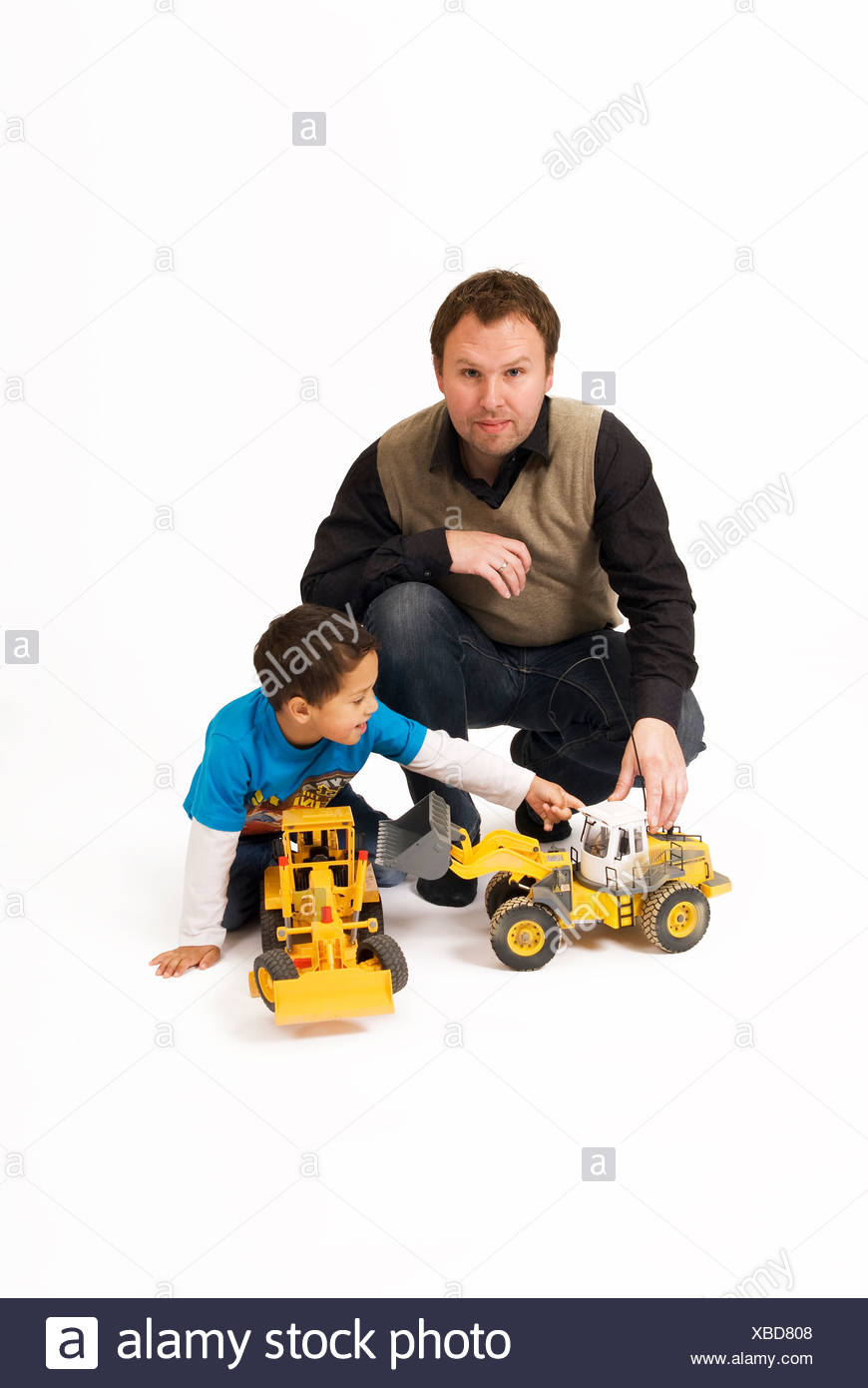 Portrait of a man by son playing with toy vehicles against white background Stock Photo