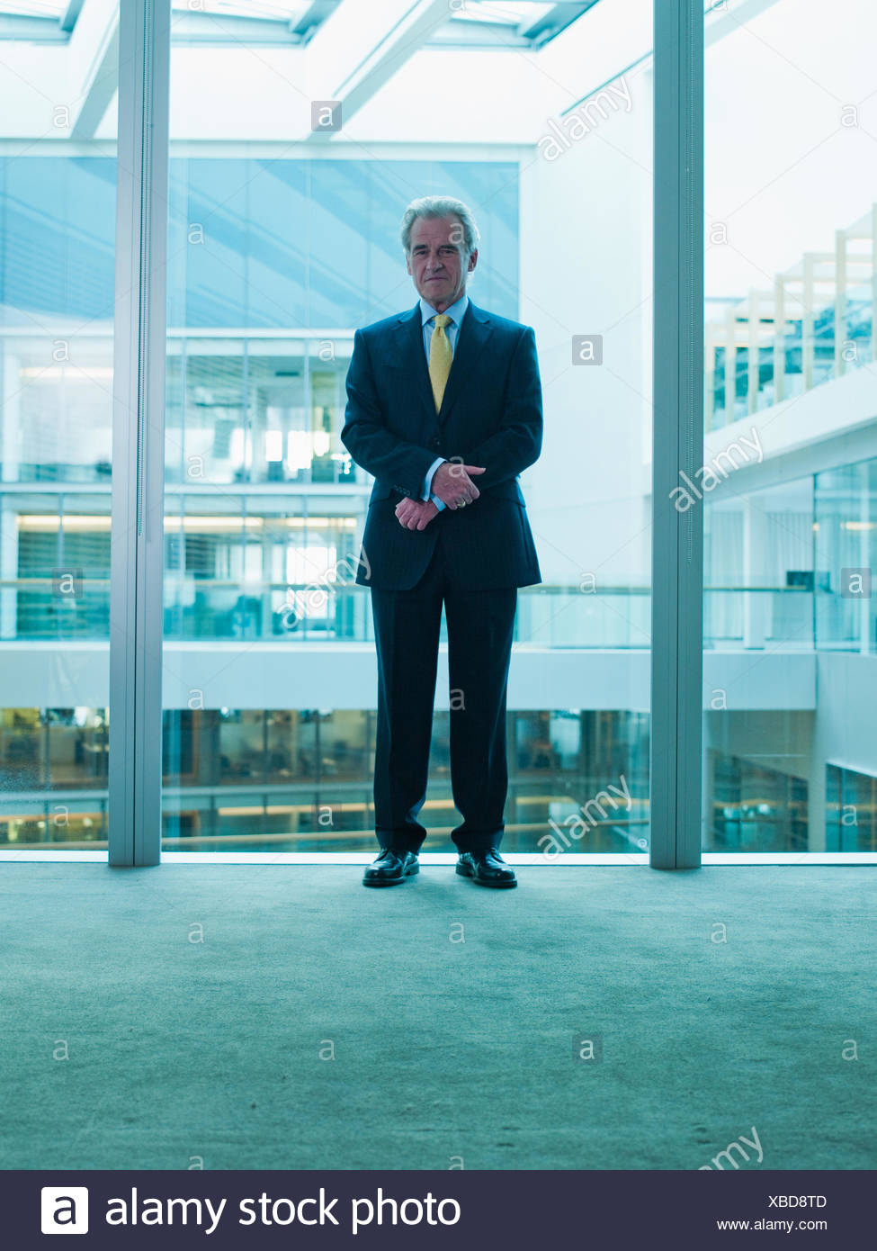 Businessman standing glass wall in office - Stock Image