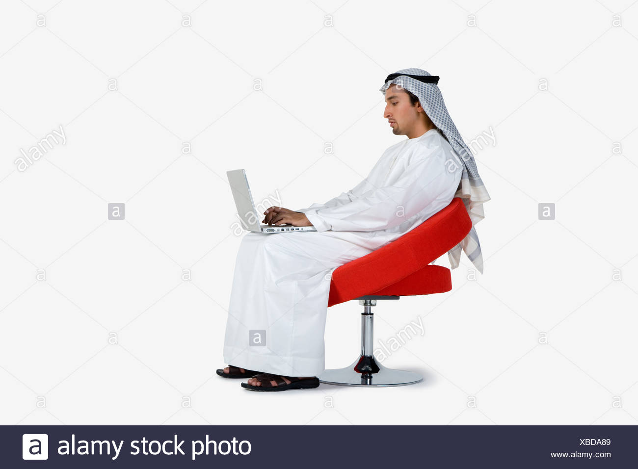 Young man sitting on chair, using laptop Stock Photo