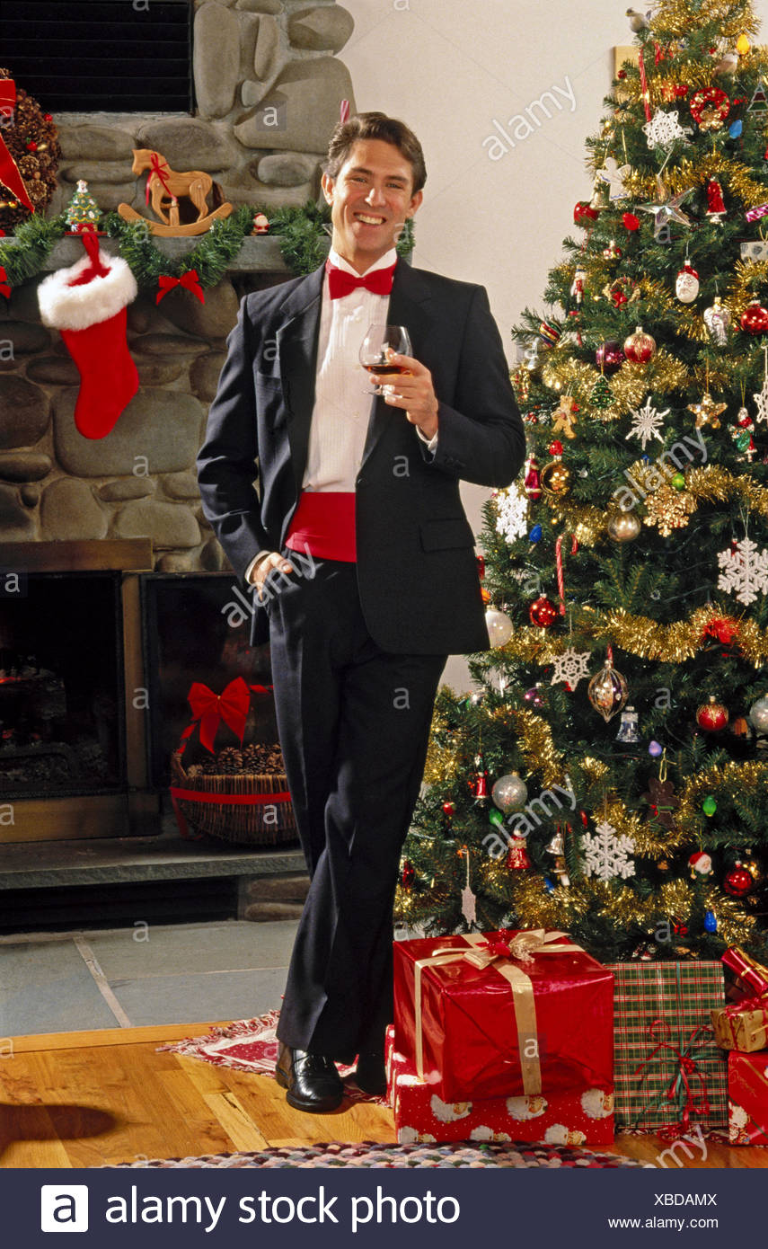 Man in tux by Christmas tree - Stock Image