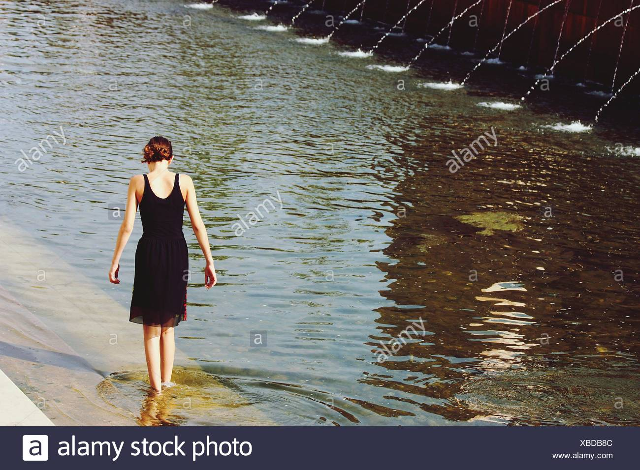 Rear View Of Woman Standing At Dam - Stock Image