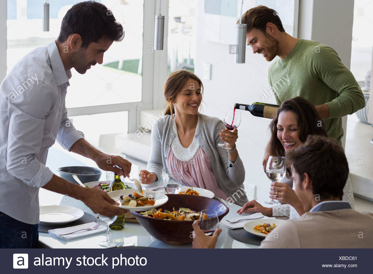 Man serving food to his friends at dining table - Stock Image