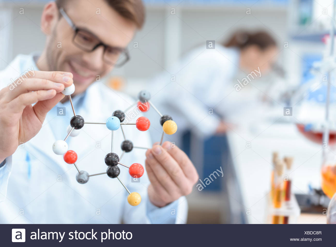 Smiling man scientist in eyeglasses holding molecular model in lab - Stock Image