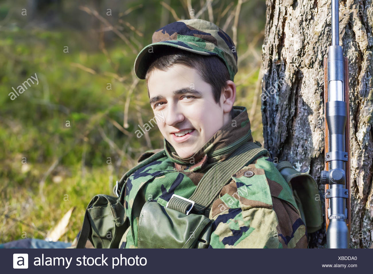Young recruit with optical rifle in forest - Stock Image