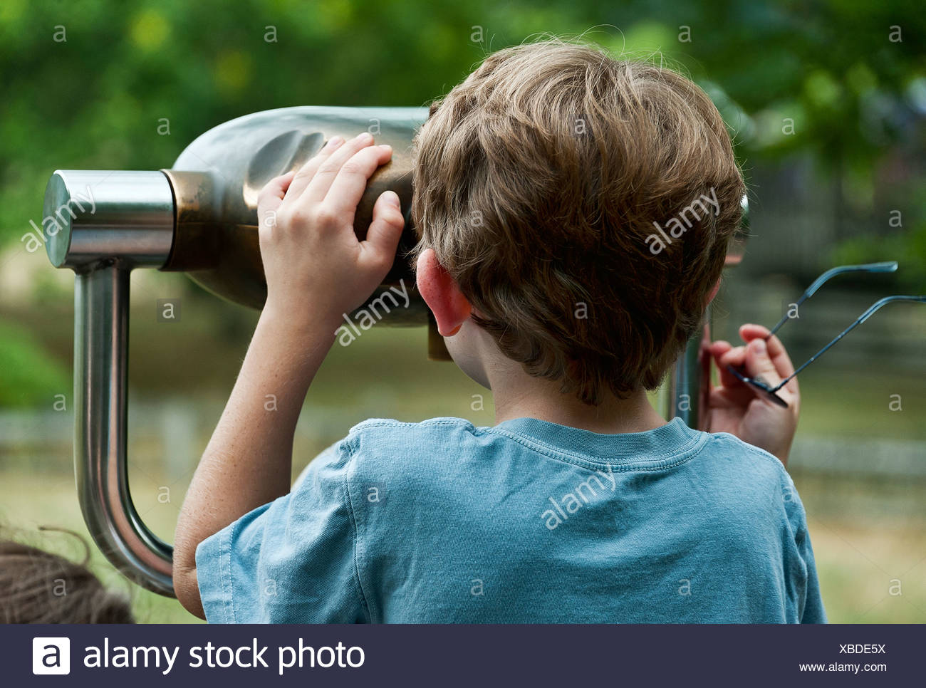 Boy looking through a viewing scope. - Stock Image