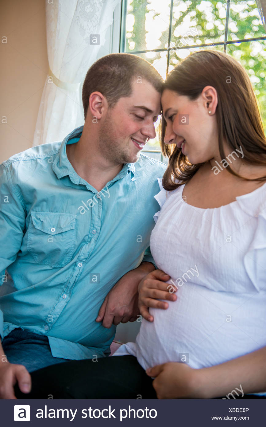 Pregnant woman face to face with partner - Stock Image