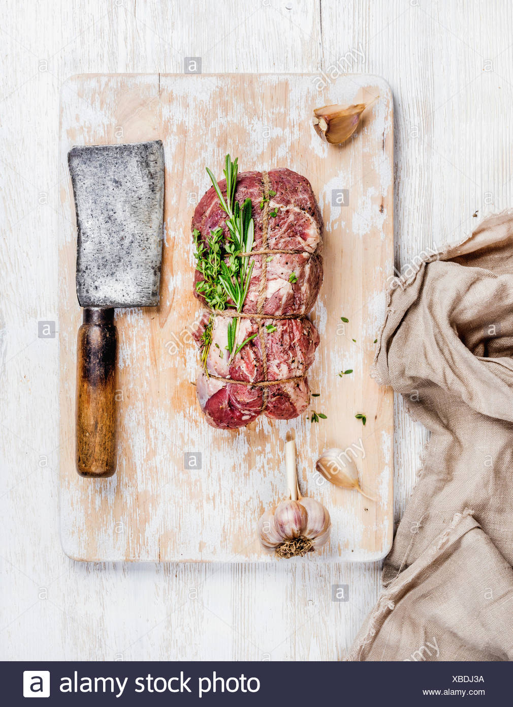 Raw uncooked roastbeef meat cut with rosemary, thyme and garlic and butcher knife on old white painted wooden background, top vi - Stock Image