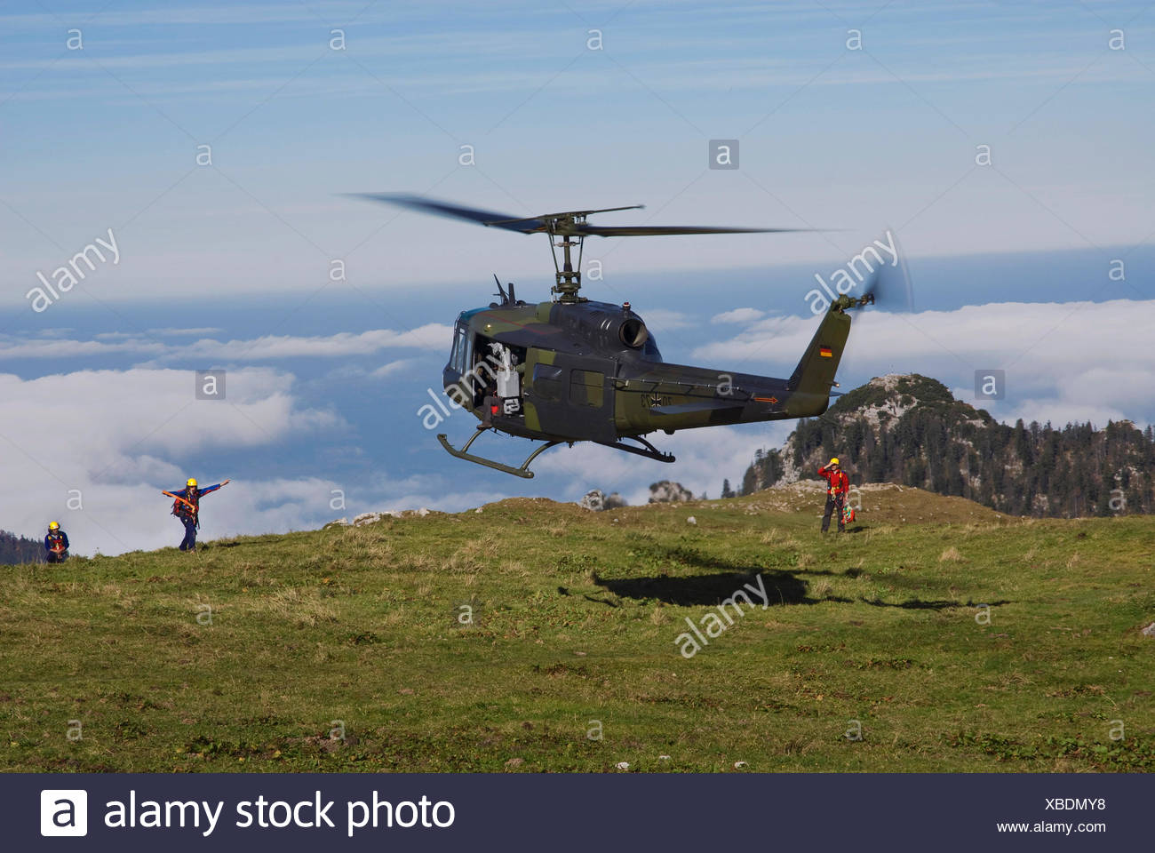 Landing Bundeswehr military helicopter marshalled by rescue personnel, Bavarian Alps, Upper Bavaria, Bavaria - Stock Image