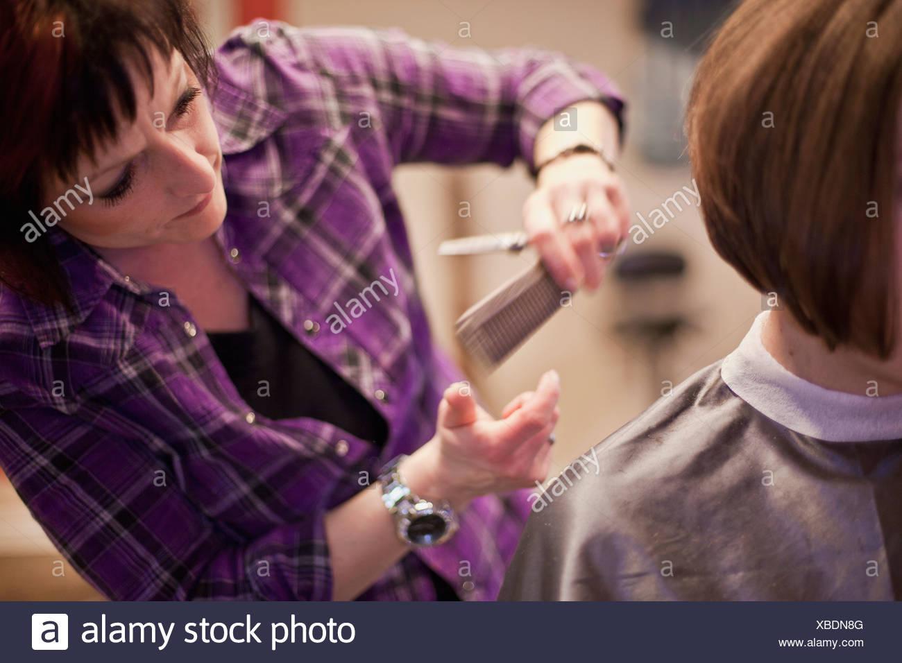 Woman cutting hair of customer - Stock Image