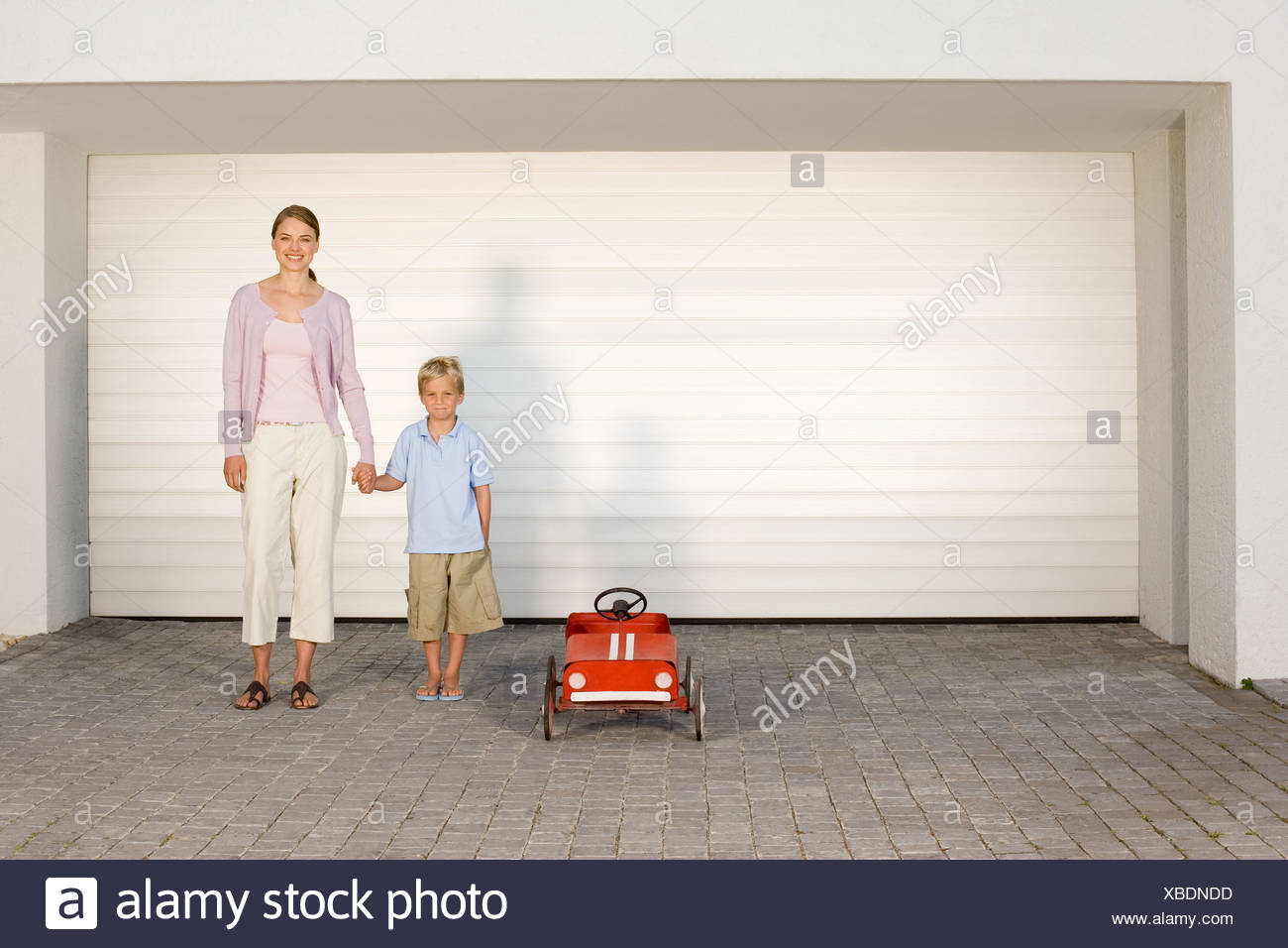Mother and son stood by toy car - Stock Image
