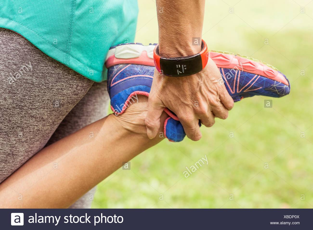 Mature woman, holding foot, stretching, mid section - Stock Image