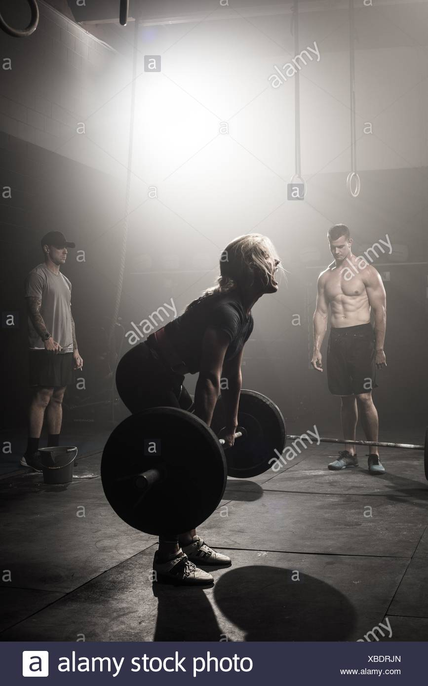 Young woman preparing to lift barbell - Stock Image