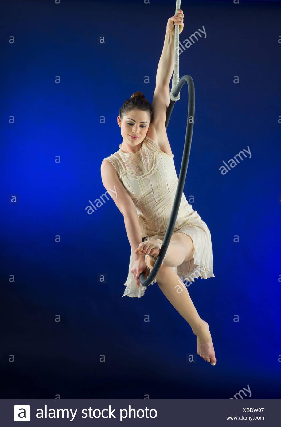 Aerialist poised on hoop against blue background Stock Photo