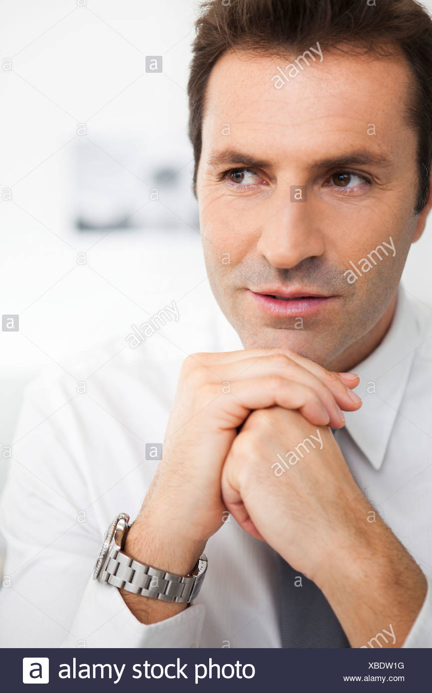 Businessman with hands clasped under chin, portrait - Stock Image