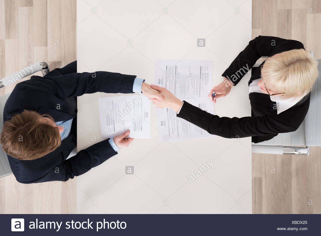 Businesspeople Shaking Hand At Desk - Stock Image