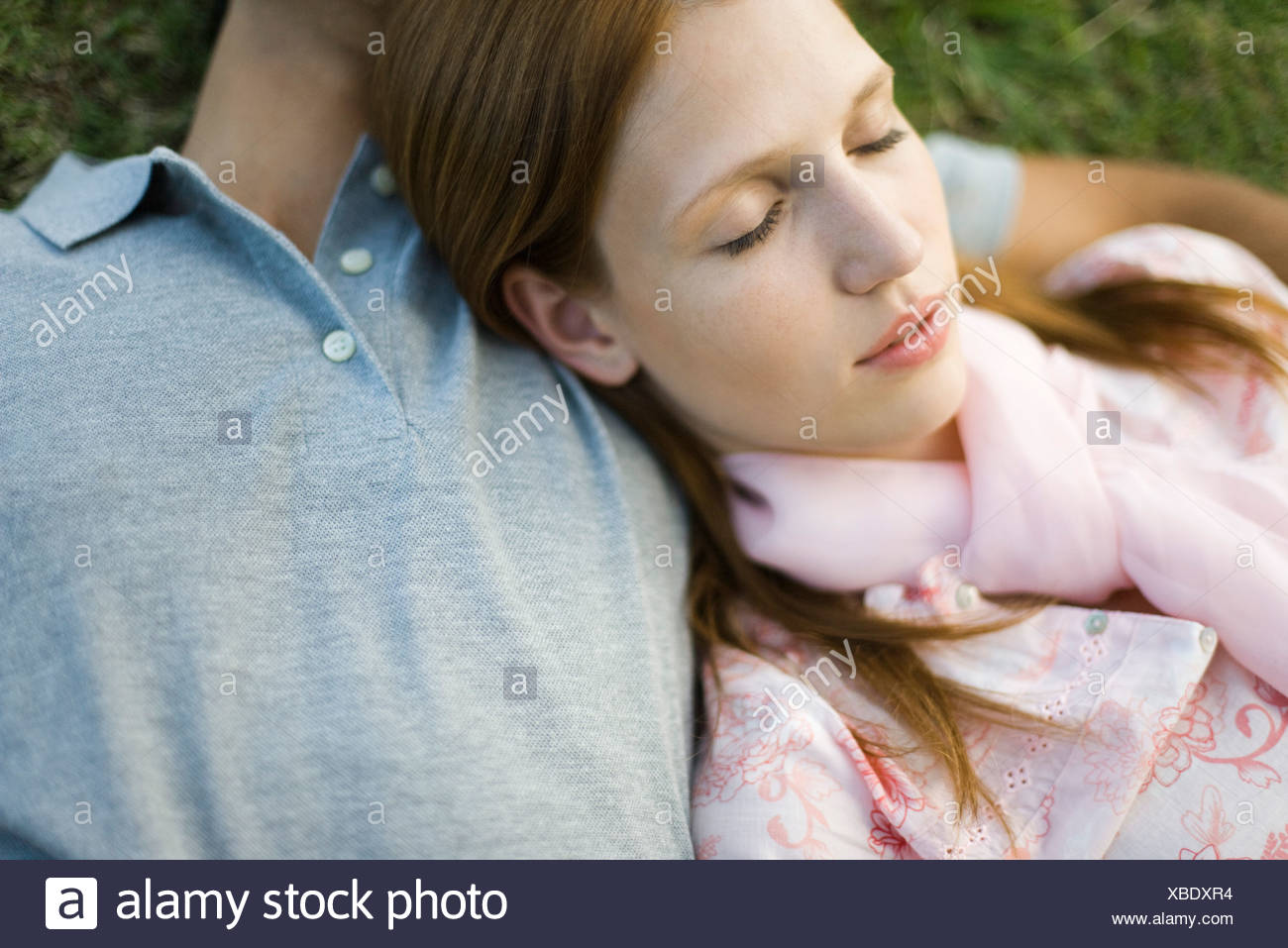 Young couple napping on ground, woman's head resting on man's chest - Stock Image
