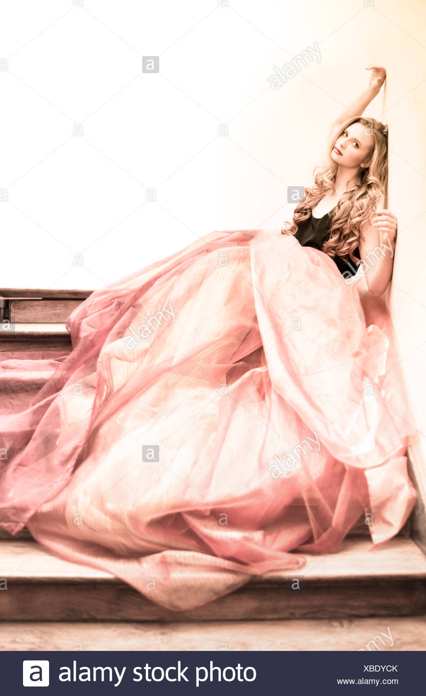Portrait of young woman at staircase wearing Haute Couture - Stock Image