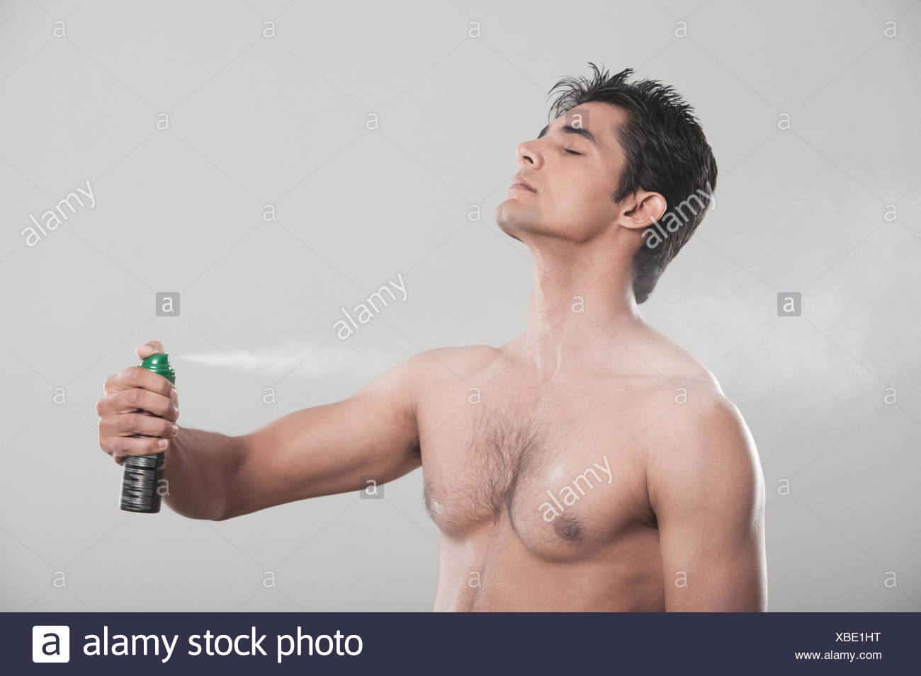 Man applying deodorant over his body - Stock Image