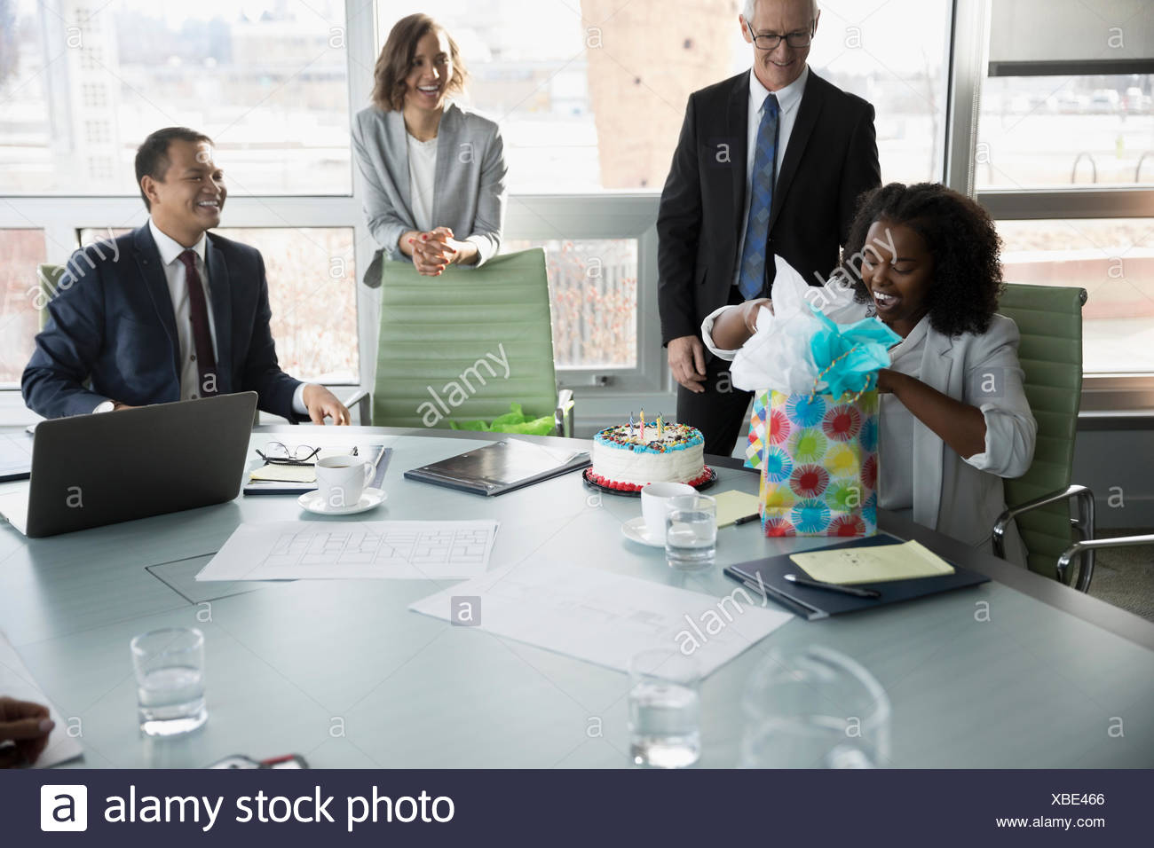 Businesswoman Opening Birthday Gifts From Colleagues In Conference Room