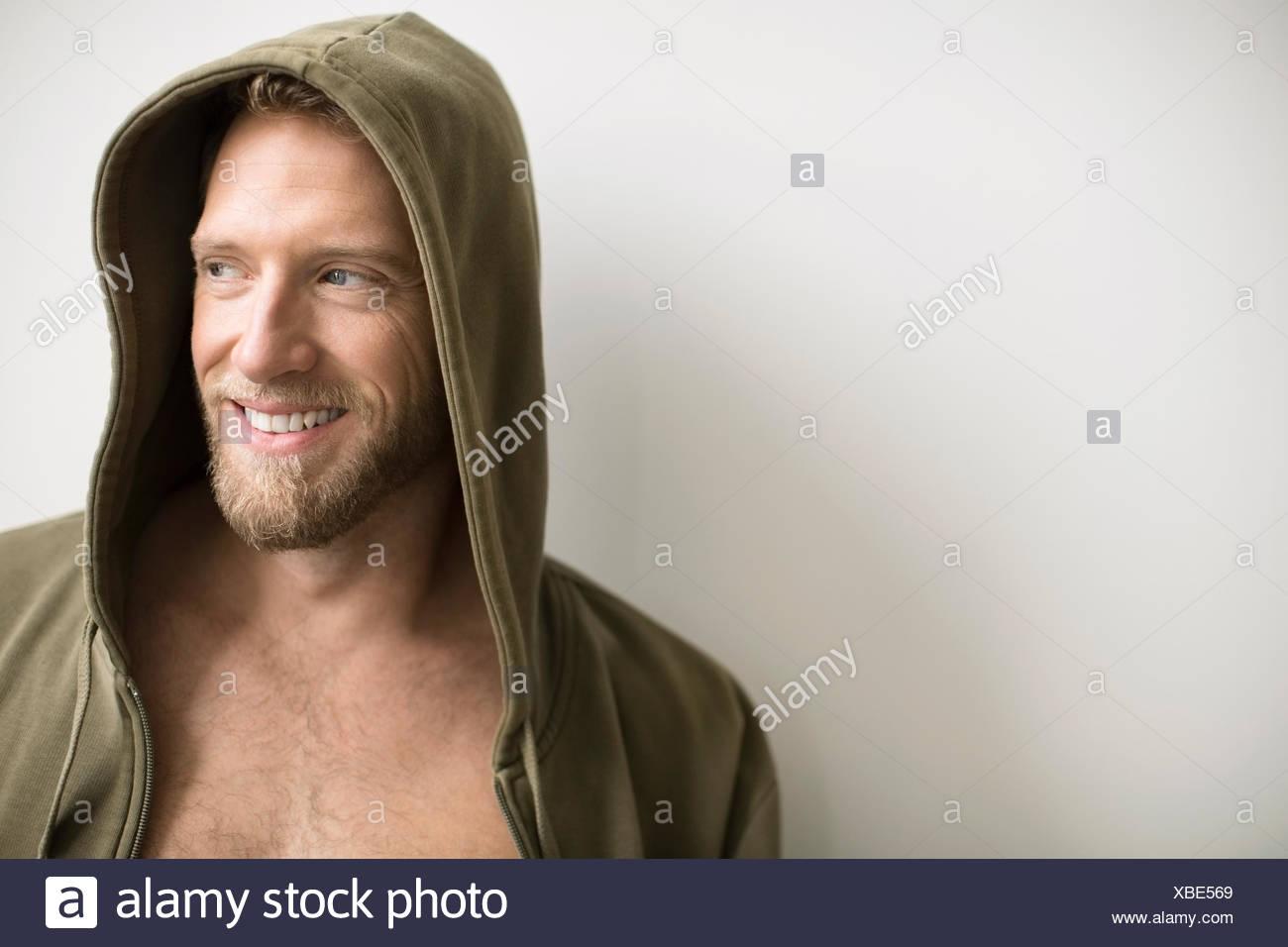 Smiling man with beard wearing hoody - Stock Image