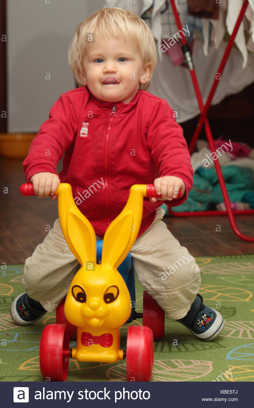 Portrait of an eighteen-months-old baby girl riding on a toy. - Stock Image