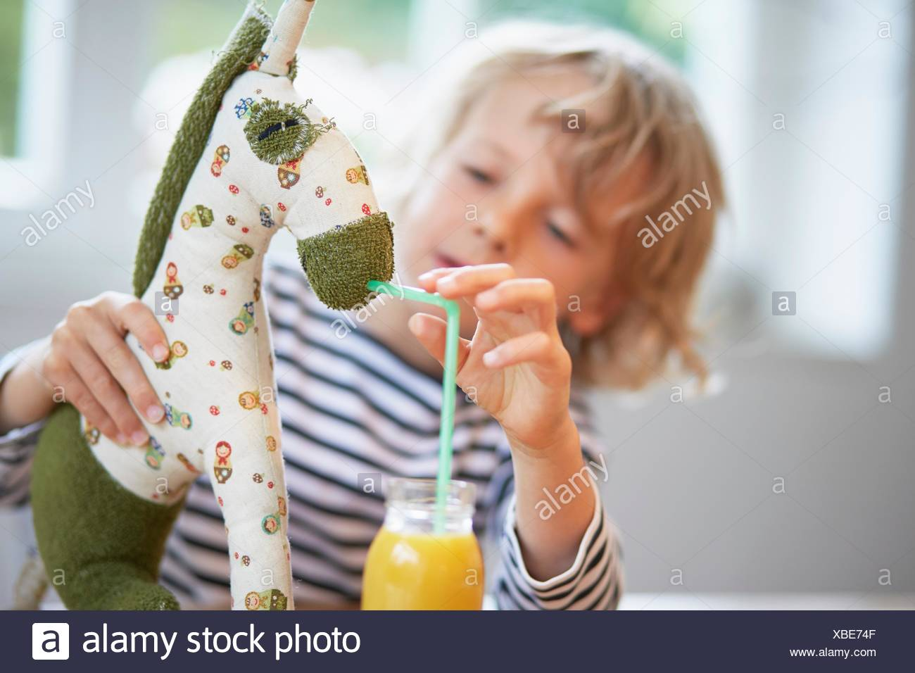 Young boy pretending to feed drink to soft toy - Stock Image