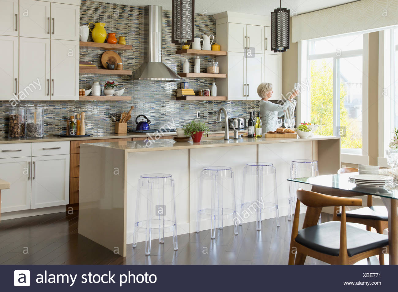 Woman cleaning wine glasses in kitchen - Stock Image