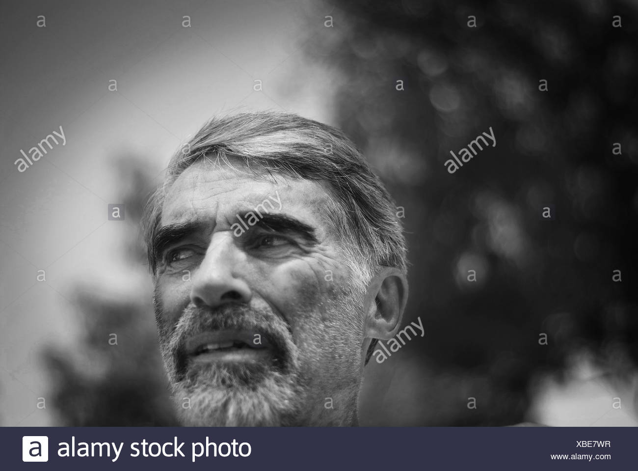 Pensive senior man looking off camera with a skeptical worried anxious look on his face - Stock Image