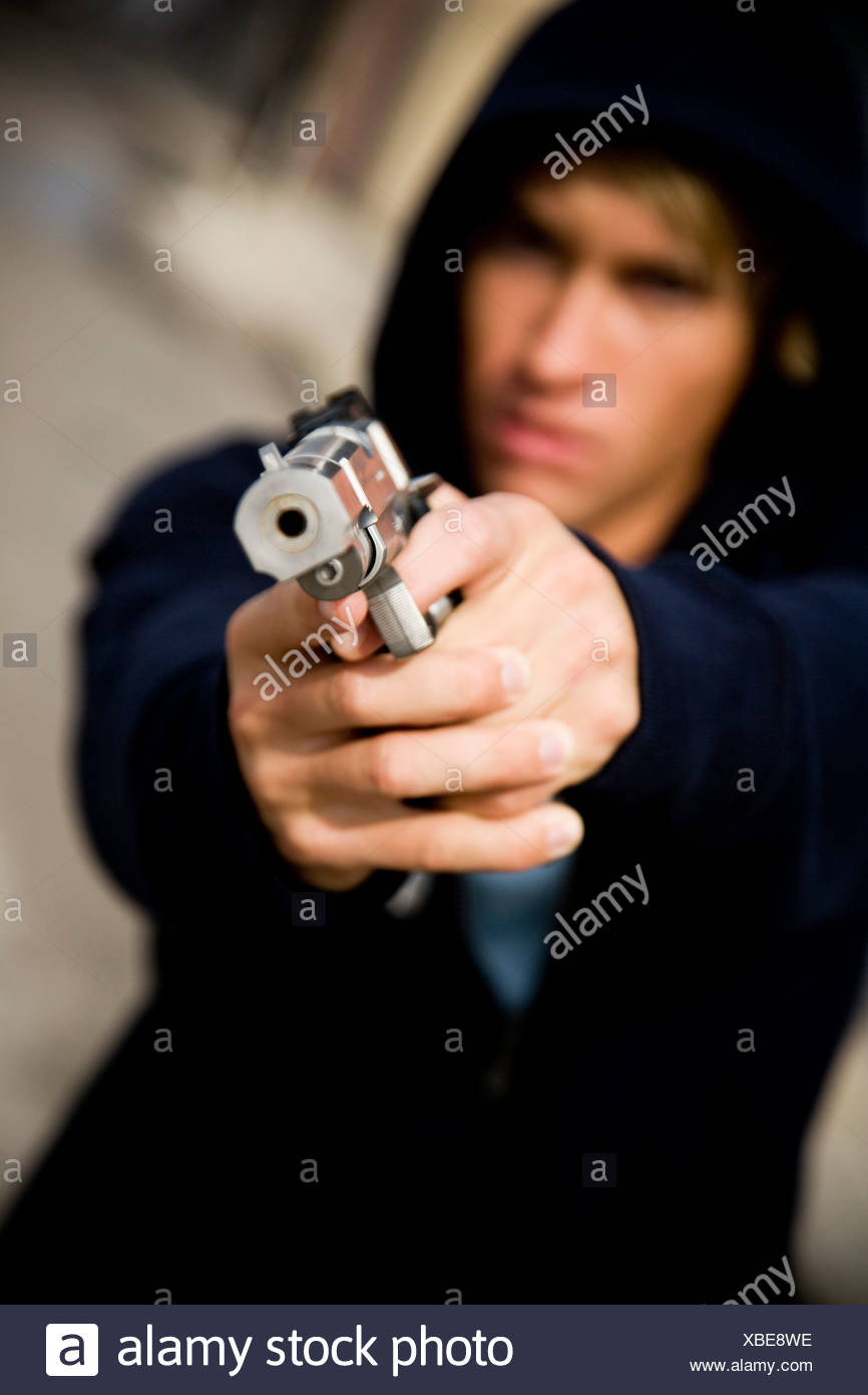 Portrait of a young man holding a gun - Stock Image
