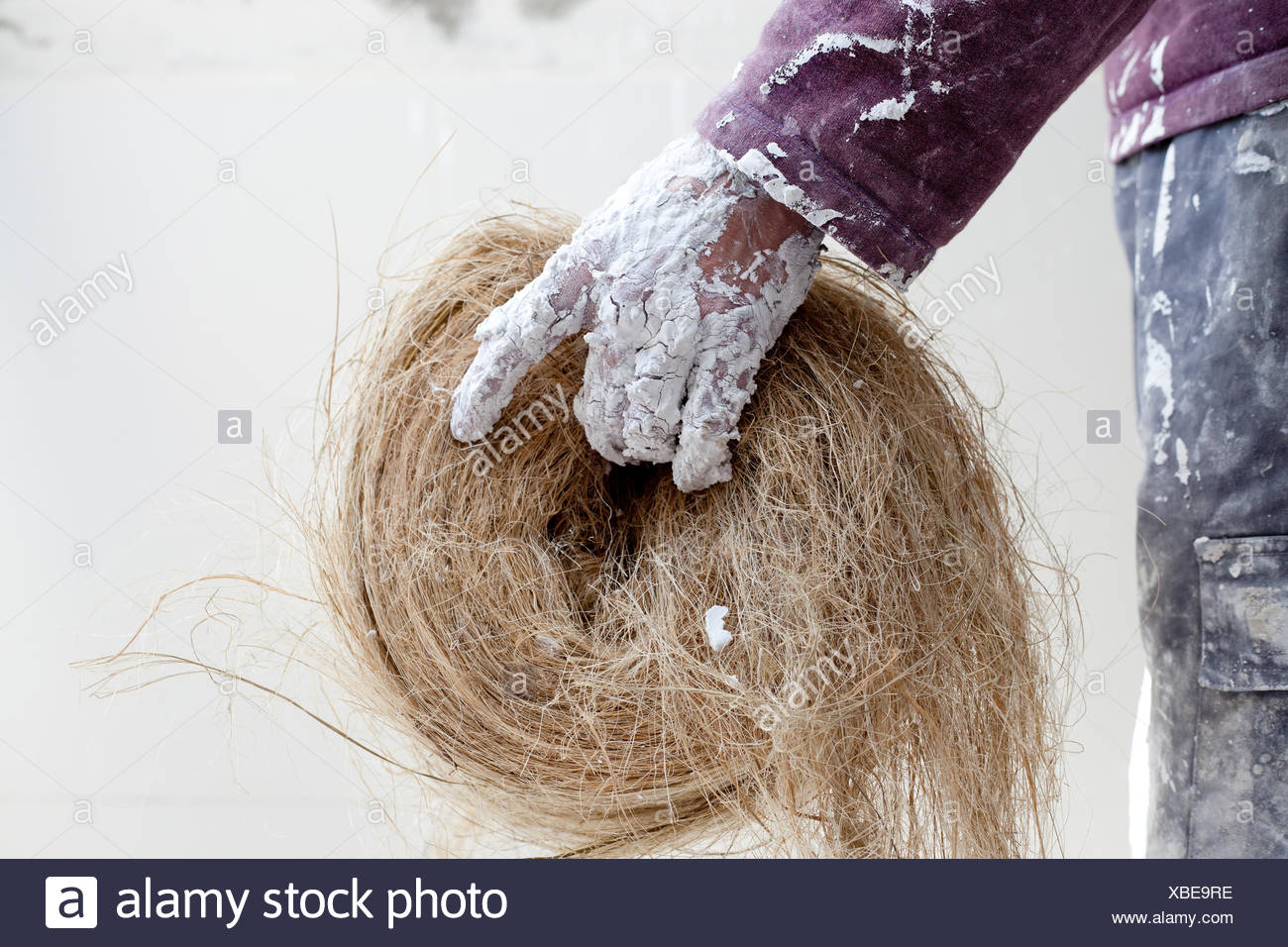 Plaster dirty hand with hemp for plasterboard Stock Photo