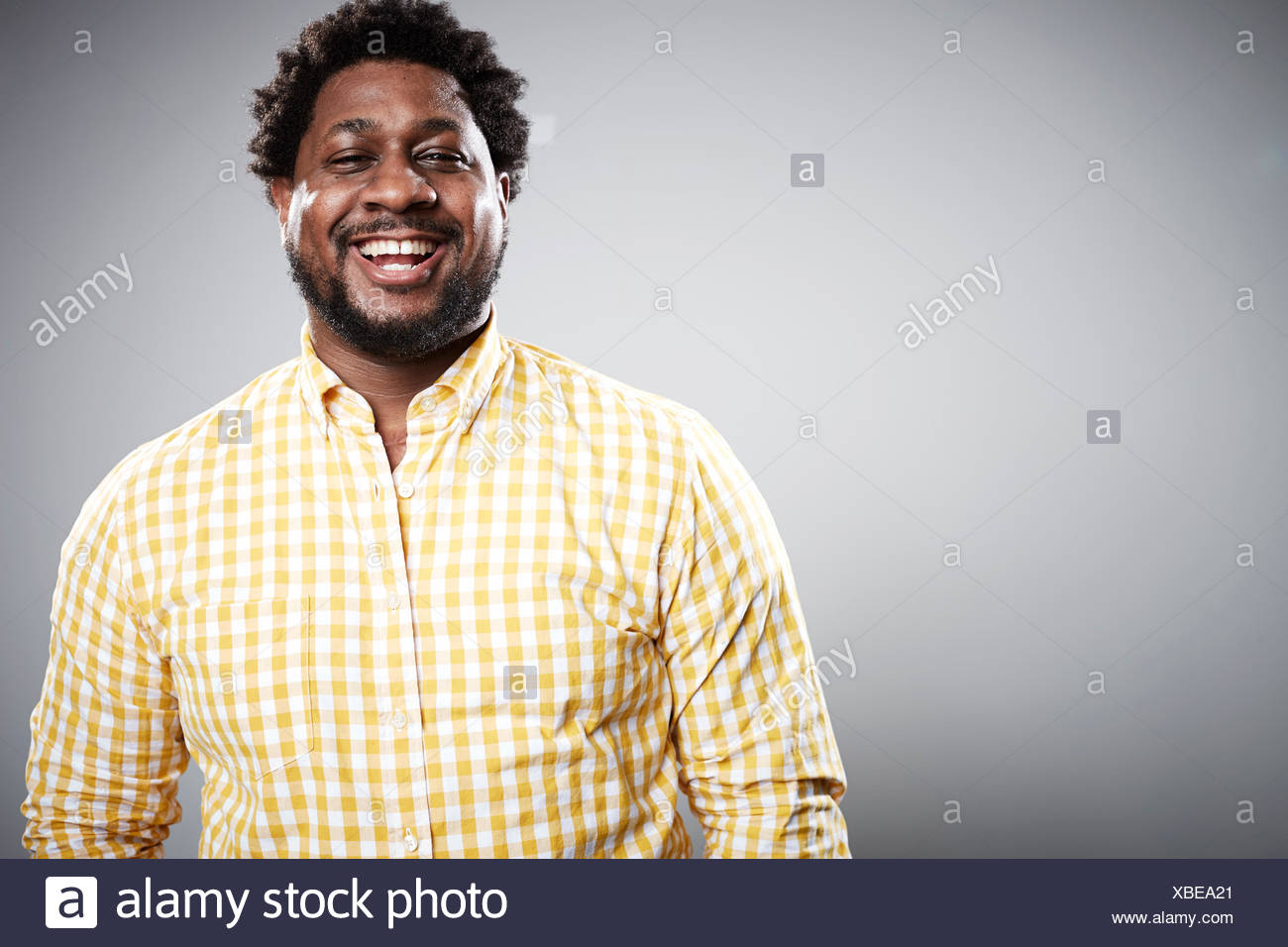 Studio portrait of mid adult businessman laughing - Stock Image