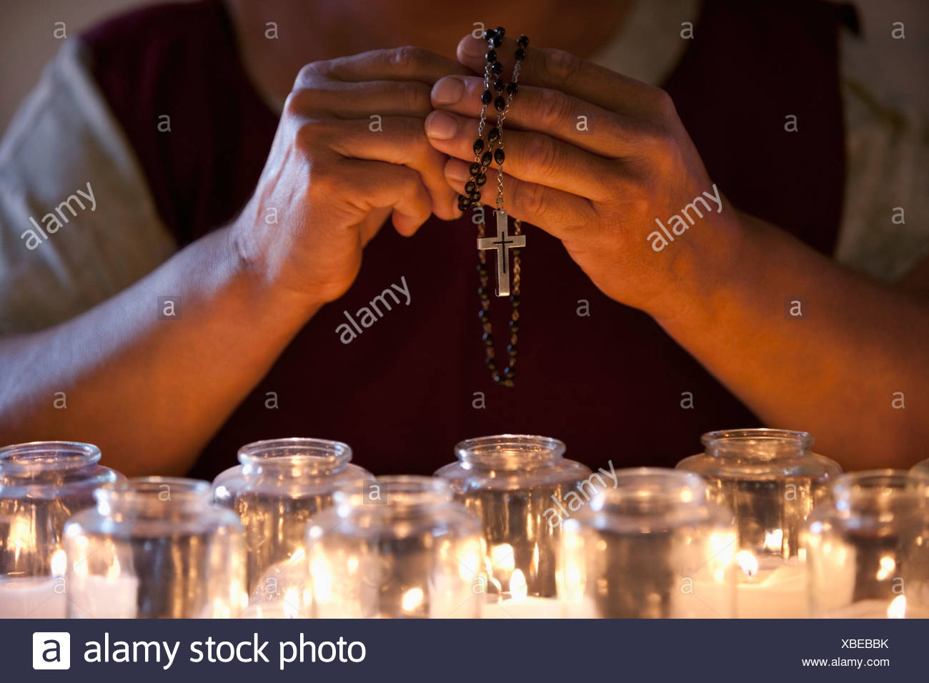 Hands holding prayer beads over candles - Stock Image