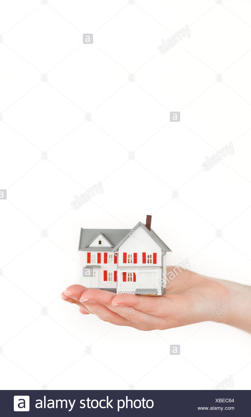 Hand holding a miniature house on a white background - Stock Image