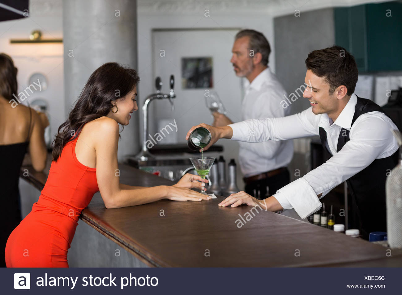 Waiter pouring cocktail into cocktail glass - Stock Image