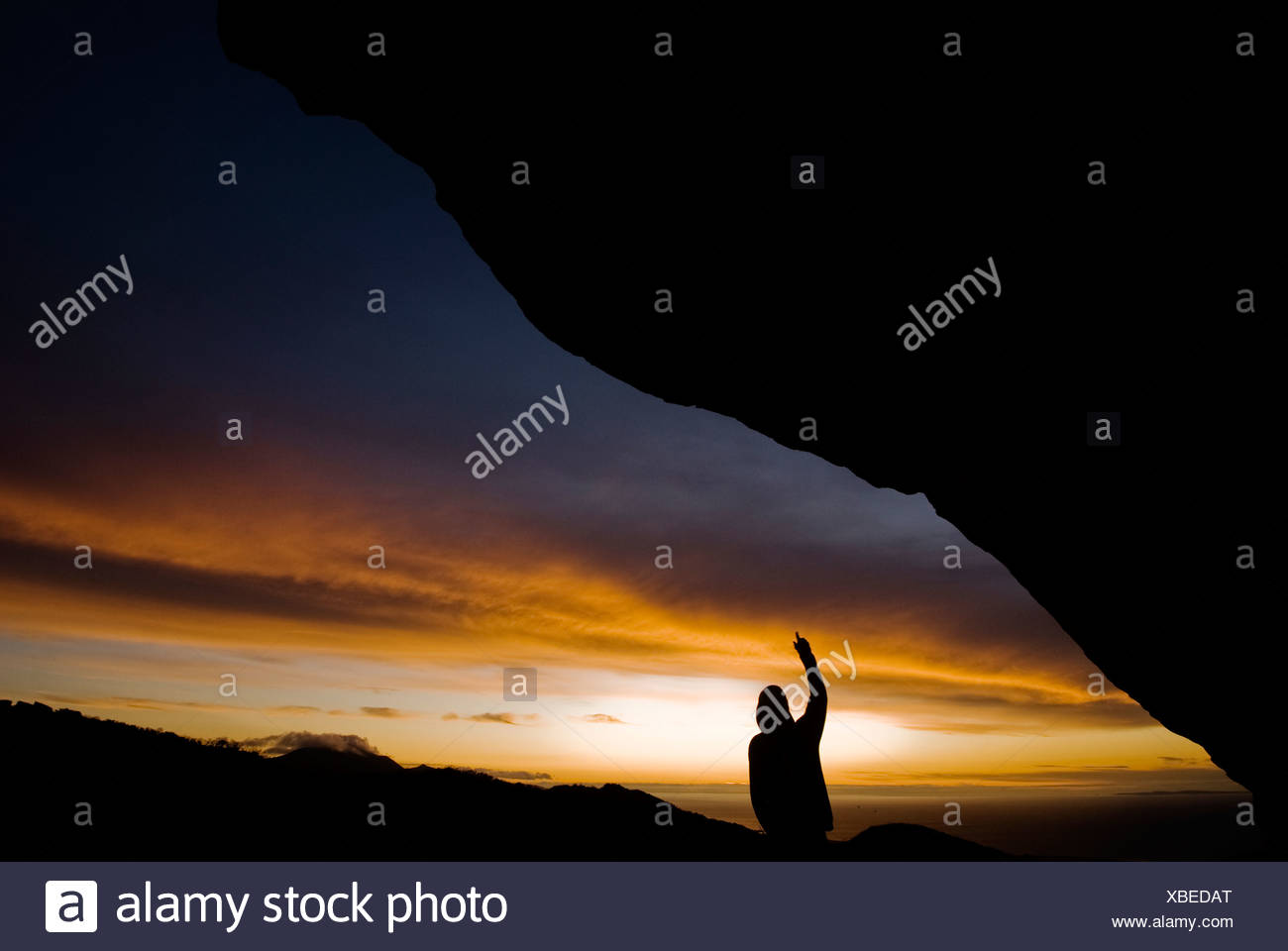A young man points out a line to rock climb on a giant over hanging natural rock wall. - Stock Image