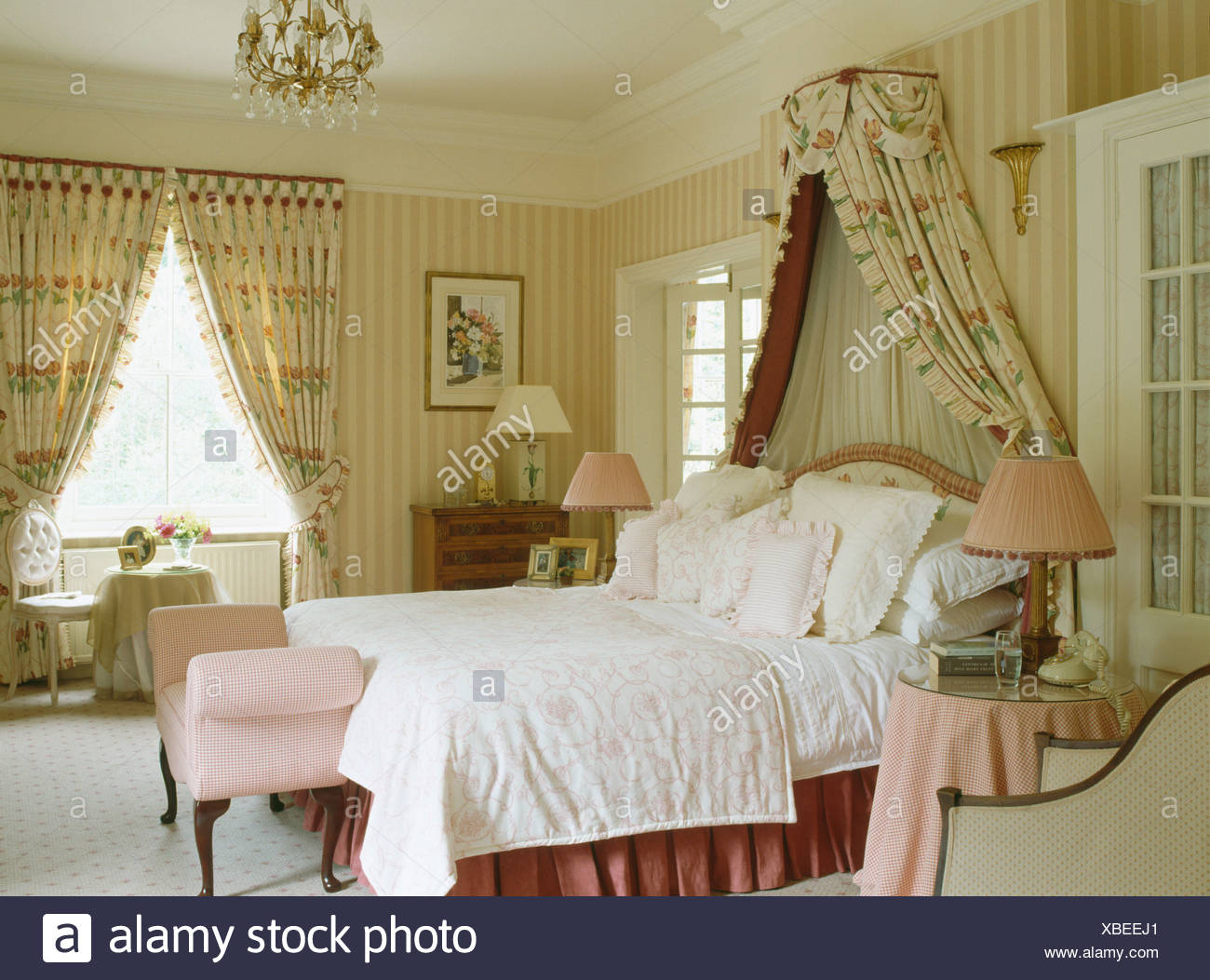 Coronet With Floral Drapes Above Bed Piled With Cushions In Country Bedroom With Striped Wallpaper And Floral Curtains Stock Photo Alamy