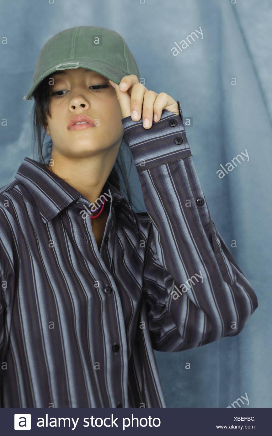 Teenage girl wearing large button down shirt and baseball cap, portrait - Stock Image