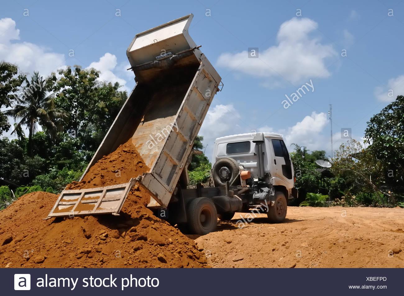 White dump truck dumping soil in my home ground. - Stock Image